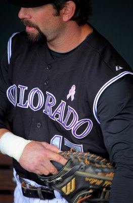DENVER - MAY 10:  Todd Helton #17 of the Colorado Rockies prepares to take the field as his uniform displays a pink MLB logo and pink ribbon that adorned the players uniforms as part of Major League Baseball's 'Going To Bat Against Breast Cancer' promotio