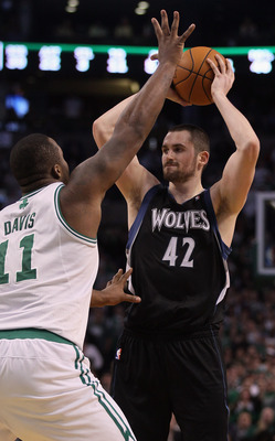 BOSTON, MA - JANUARY 03:  Kevin Love #42 of the Minnesota Timberwolves looks to pass as Glen Davis #11 of the Boston Celtics defends on January 3, 2011 at the TD Garden in Boston, Massachusetts. The Celtics defeated the Timberwolves 96-93. NOTE TO USER: U