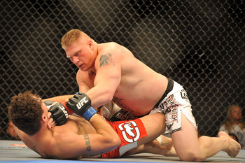 LAS VEGAS - JULY 11:  Brock Lesnar holds down Frank Mir during their heavyweight title bout during UFC 100 on July 11, 2009 in Las Vegas, Nevada. Lesnar defeated Mir by a second round knockout.  (Photo by Jon Kopaloff/Getty Images)