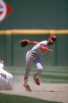 SAN DIEGO - 1985:  Ozzie Smith #1 of the St. Louis Cardinals stumbles after dodging a sliding San Diego Padres base runner during a game in 1985 at Jack Murphy Stadium in San Diego, California.  (Photo by Stephen Dunn/Getty Images)