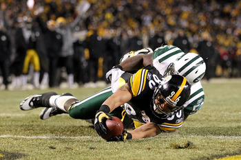 PITTSBURGH, PA - JANUARY 23:  Hines Ward #86 of the Pittsburgh Steelers catches the ball and is down on the one-yard line as he is tackled by David Harris #52 of the New York Jets during the 2011 AFC Championship game at Heinz Field on January 23, 2011 in