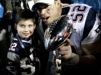 JACKSONVILLE, FL - FEBRUARY 06:  Ted Johnson #52 of the New England Patriots poses with his son after defeating the Philadelphia Eagles in Super Bowl XXXIX at Alltel Stadium on February 6, 2005 in Jacksonville, Florida.  The Patriots defeated the Eagles 2