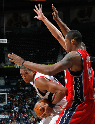 ATLANTA, GA - DECEMBER 07:  Al Horford #15 of the Atlanta Hawks drives against Derrick Favors #14 of the New Jersey Nets at Philips Arena on December 7, 2010 in Atlanta, Georgia.  NOTE TO USER: User expressly acknowledges and agrees that, by downloading a