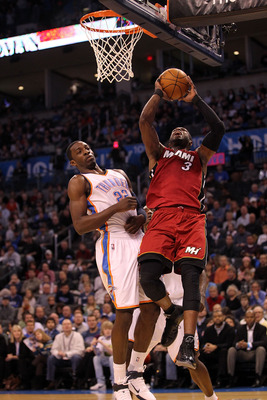 OKLAHOMA CITY, OK - JANUARY 30:  Guard Dwyane Wade #3 of the Miami Heat takes a shot against Jeff Green #22 of the Oklahoma City Thunder at Ford Center on January 30, 2011 in Oklahoma City, Oklahoma.  NOTE TO USER: User expressly acknowledges and agrees t