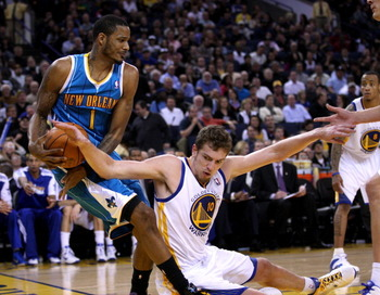 OAKLAND, CA - JANUARY 26:  Trevor Ariza #1 of the New Orleans Hornets and David Lee #10 of the Golden State Warriors go for the ball at Oracle Arena on January 26, 2011 in Oakland, California.  NOTE TO USER: User expressly acknowledges and agrees that, by