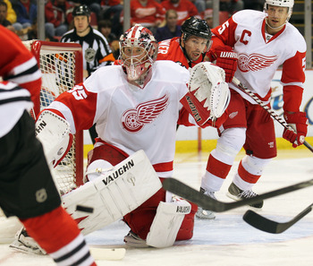DETROIT, MI - JANUARY 22:  Jimmy Howard #35 of the Detroit Rewd Wings keeps an eye on an incoming puck in a game against the Chicago Black Hawks on January 22, 2011 at the Joe Louis Arena in Detroit, Michigan. The Hawks defeated the Wings 4-1. (Photo by C