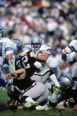 LOS ANGELES, CA - DECEMBER 15:  Defensive tackle Joe Nash #72 of the Seattle Seahawks tackles Los Angeles Raiders running back Marcus Allen #32 during the game at Los Angeles Memorial Coliseum on December 15, 1985 in Los Angeles, California.  The Raiders