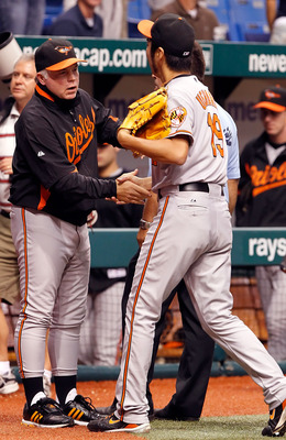 ST. PETERSBURG, FL - SEPTEMBER 29:  Manager Buck Showalter of the Baltimore Orioles congratulates relief pitcher Koji Uehara #19 for his save against the Tampa Bay Rays at Tropicana Field on September 29, 2010 in St. Petersburg, Florida.  (Photo by J. Mer