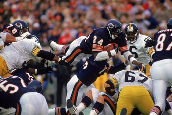 Walter Payton #34 of the Chicago Bears carries the ball as he jumps over the line during a game against the Pittsburgh Steelers.