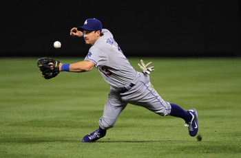 DENVER - SEPTEMBER 27:  Second baseman Ryan Theriot #13 of the Los Angeles Dodgers makes the stop on a ground ball by Todd Helton of the Colorado Rockies but looses the handle on the ball and is unable to throw out Helton at Coors Field on September 25, 2