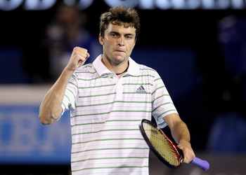 MELBOURNE, AUSTRALIA - JANUARY 19:  Gilles Simon of France celebrates a set point in his second round match against Roger Federer of Switzerland during day three of the 2011 Australian Open at Melbourne Park on January 19, 2011 in Melbourne, Australia.  (