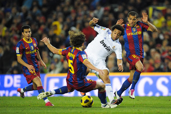 BARCELONA, SPAIN - NOVEMBER 29:  Marcelo Vieira of Real Madrid (2ndR) vies for the ball against Carles Puyol (2ndL) and Dani Alves (R) of Barcelona during the La Liga match between Barcelona and Real Madrid at the Camp Nou Stadium on November 29, 2010 in