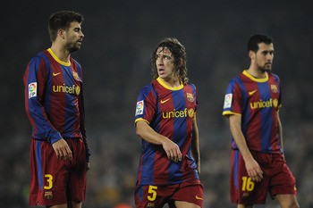 BARCELONA, SPAIN - JANUARY 16:  Gerard Pique (L), Carles Puyol (C) and Sergio Busquets of FC Barcelona look on during the La Liga match between FC Barcelona and Malaga at Nou Camp on January 16, 2011 in Barcelona, Spain. Barcelona won 4-1.  (Photo by Davi