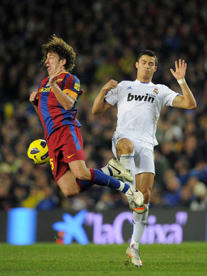 BARCELONA, SPAIN - NOVEMBER 29:  Carles Puyol of Barcelona (L) vies for the ball with Cristiano Ronaldo of Real Madrid during the La Liga match between Barcelona and Real Madrid at the Camp Nou Stadium on November 29, 2010 in Barcelona, Spain.  Barcelona