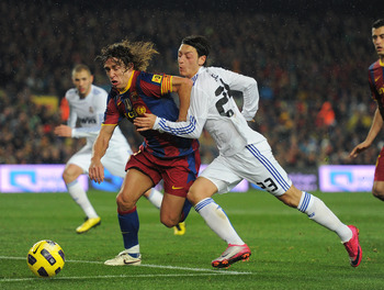 BARCELONA, SPAIN - NOVEMBER 29:  Mesut Ozil (R) of Real Madrid duels for the ball with Carles Puyol of Barcelona during the la liga match between Barcelona and Real Madrid at the Camp Nou stadium on November 29, 2010 in Barcelona, Spain.  (Photo by Jasper