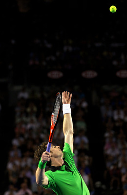 MELBOURNE, AUSTRALIA - JANUARY 30:  Andy Murray of Great Britain serves in the men's final match against Novak Djokovic of Serbia during day fourteen of the 2011 Australian Open at Melbourne Park on January 30, 2011 in Melbourne, Australia.  (Photo by Qui