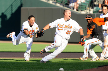 BALTIMORE - SEPTEMBER 19:  Ty Wigginton #23 of the Baltimore Orioles is chased by Robert Andino #12 after driving in the game winning run in the eleventh inning against the New York Yankees at Camden Yards on September 19, 2010 in Baltimore, Maryland. The