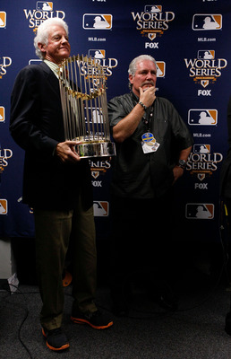 ARLINGTON, TX - NOVEMBER 01:  Owner of the San Francisco Giants, William H. Neukom, holds the World Series trophy in the locker room next to Giants' general manager Brian Sabean after the Giants defeated the Texas Rangers 3-1 in Game Five of the 2010 MLB