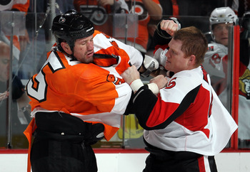 PHILADELPHIA, PA - JANUARY 20:  Chris Neil #25 of the Ottawa Senators trades punches with Jody Shelley #45 of the Philadelphia Flyers during the third period on January 20, 2011 at Wells Fargo Center in Philadelphia, Pennsylvania. The Flyers defeated the