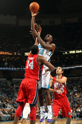 NEW ORLEANS, LA - DECEMBER 22:  Emeka Okafor #50 of the New Orleans Hornets shoots the ball over Derrick Favors #14 of the New Jersey Nets at the New Orleans Arena on December 22, 2010 in New Orleans, Louisiana.  The Hornets defeated the Nets 105-91.   NO