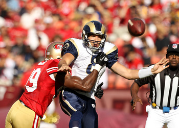SAN FRANCISCO - NOVEMBER 14:  Sam Bradford #8  of the St. Louis Rams is hit by Manny Lawson #99 of the San Francisco 49ers at Candlestick Park on November 14, 2010 in San Francisco, California.  (Photo by Ezra Shaw/Getty Images)
