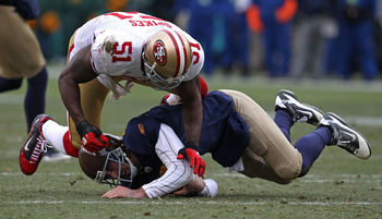 GREEN BAY, WI - DECEMBER 05: Takeo Spikes #51 of the San Francisco 49ers hits Aaron Rodgers #12 of the Green Bay Packers at Lambeau Field on December 5, 2010 in Green Bay, Wisconsin. The Packers defeated the 49ers 34-16. (Photo by Jonathan Daniel/Getty Im