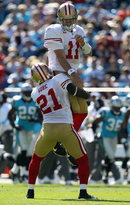 CHARLOTTE, NC - OCTOBER 24:  Frank Gore #21 of the San Francisco 49ers holds up his teammate Alex Smith #11 after a touchdown against the Carolina Panthers during their game at Bank of America Stadium on October 24, 2010 in Charlotte, North Carolina.  (Ph