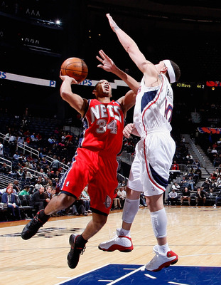 ATLANTA, GA - DECEMBER 07:  Devin Harris #34 of the New Jersey Nets drives against Mike Bibby #10 of the Atlanta Hawks at Philips Arena on December 7, 2010 in Atlanta, Georgia.  NOTE TO USER: User expressly acknowledges and agrees that, by downloading and