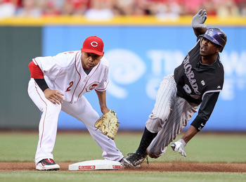 CINCINNATI - JULY 17:  Dexter Fowler #24 of the Colorado Rockies slides safely in front of the tag by Orlando Cabrera #2 of the Cincinnati Reds during the game at Great American Ball Park on July 17, 2010 in Cincinnati, Ohio.  (Photo by Andy Lyons/Getty I