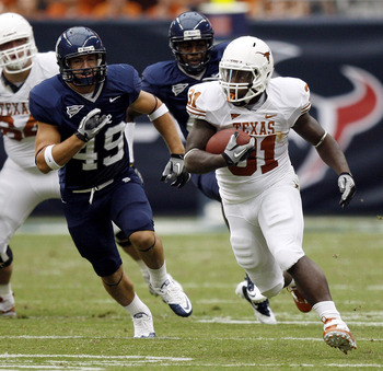 HOUSTON - SEPTEMBER 04:  Running back Cody Johnson #31 of the Texas Longhorns rushes past linebacker Trey Briggs #49 of the Rice Owls in the second quarter at Reliant Stadium on September 4, 2010 in Houston, Texas.  (Photo by Bob Levey/Getty Images)