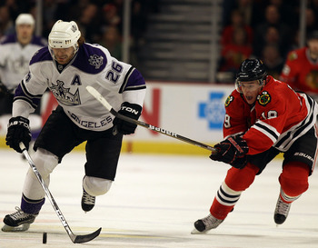 CHICAGO, IL - DECEMBER 19: Michal Handzus #26 of the Los Angeles Kings skates up the ice under pressure from Jonathan Toews #19 of the Chicago Blackhawks at the United Center on December 19, 2010 in Chicago, Illinois. (Photo by Jonathan Daniel/Getty Image