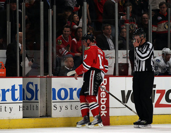 CHICAGO, IL - DECEMBER 03: Jonathan Toews #19 of the Chicago Blackhawks is escorted to the penalty box by a referee during a game against the Vancouver Canucks at the United Center on December 3, 2010 in Chicago, Illinois. The Canucks defeated the Blackha