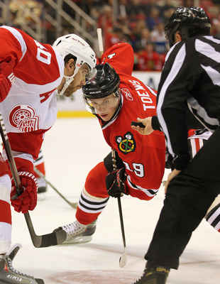 DETROIT, MI - JANUARY 22:  Jonathan Toews #19 of the Chicago Black Hawks takes a faceoff against Henrik Zetterberg #40 of the Detroit Red Wings in a game on January 22, 2011 at the Joe Louis Arena in Detroit, Michigan. The Hawks defeated the Wings 4-1. (P