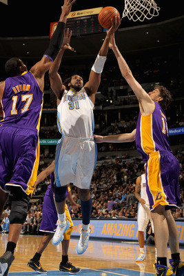 DENVER, CO - JANUARY 21:  Nene #31 of the Denver Nuggets puts up a shot between Andrew Bynum #17 and Pau Gasol #16 of the Los Angeles Lakers at the Pepsi Center on January 21, 2011 in Denver, Colorado. The Lakers defeated the Nuggets 107-97. NOTE TO USER: