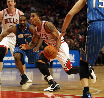 CHICAGO, IL - JANUARY 28: Derrick Rose #1 of the Chicago Bulls drives between Gilbert Arenas #1 and Hedo Turkoglu #15 of the Orlando Magic at the United Center on January 28, 2011 in Chicago, Illinois. The Bulls defeated the Magic 99-90. NOTE TO USER: Use
