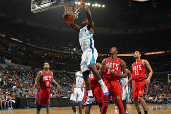 NEW ORLEANS, LA - DECEMBER 22:  Emeka Okafor #50 of the New Orleans Hornets dunks the ball over Derrick Favors #14 of the New Jersey Nets at the New Orleans Arena on December 22, 2010 in New Orleans, Louisiana.   NOTE TO USER: User expressly acknowledges
