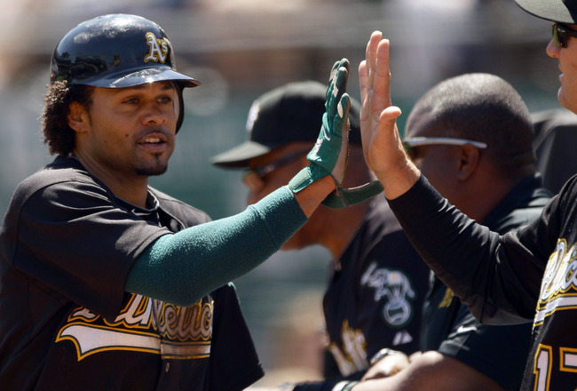 OAKLAND, CA - AUGUST 18:   Coco Crisp #4 of the Oakland Athletics is congratulated by teammates after he scored on a  Kurt Suzuki ground out in the first inning of their game against the Toronto Blue Jays at the Oakland-Alameda County Coliseum on August 1