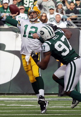 EAST RUTHERFORD, NJ - OCTOBER 31: Aaron Rodgers #12 of the Green Bay Packers throws a pass under pressure from Calvin Pace #97 of the New York Jets on October 31, 2010 at the New Meadowlands Stadium in East Rutherford, New Jersey. (Photo by Jim McIsaac/Ge