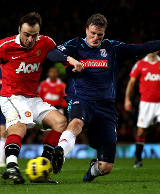 MANCHESTER, ENGLAND - JANUARY 04:  Dimitar Berbatov of Manchester United is challenged by Robert Huth of Stoke City during the Barclays Premier League match between Manchester United and Stoke City at Old Trafford on January 4, 2011 in Manchester, England