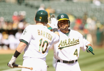 OAKLAND, CA - SEPTEMBER 06:  Coco Crisp #4 of the Oakland Athletics is congratulated by Daric Barton #10 after Crisp hit a lead off home run against the Seattle Mariners at the Oakland-Alameda County Coliseum on September 6, 2010 in Oakland, California.