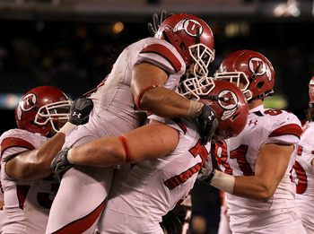 SAN DIEGO - NOVEMBER 20:  Running back Matt Asiata #4 and center Zane Taylor #77 of the Utah Utes  celebrate Asiata's one yard touchdown run against the San Diego State Aztecs in the fourth quarter at Qualcomm Stadium on November 20, 2010 in San Diego, Ca
