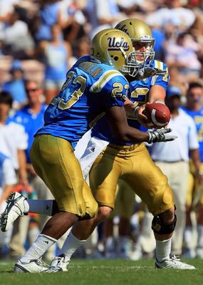 PASADENA, CA - OCTOBER 02:  Quarterback Richard Brehaut #12 of the UCLA Bruins hands off to Johnathan Franklin #23 against the Washington State Cougars during the game at the Rose Bowl on October 2, 2010 in Pasadena, California. UCLA defeated Washington S
