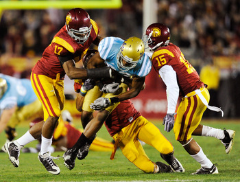 LOS ANGELES, CA - NOVEMBER 28:  Nelson Rosario #83 of the UCLA Bruins is surrounded by USC Trojans defenders after catching a pass during the second quarter of the NCAA college football game at Los Angeles Memorial Coliseum on November 28, 2009 in Los Ang