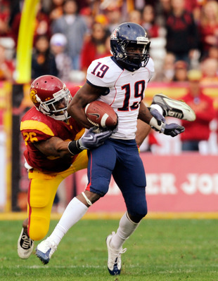 LOS ANGELES, CA - DECEMBER 05:  Wide receiver William Wright #19 of the Arizona Wildcats breaks a tackle by strong safety Will Harris #26 of the USC Trojans for a 26-yard gain during the second quarter of the NCAA college football game at the Los Angeles