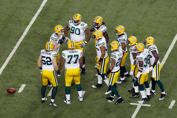 ATLANTA, GA - JANUARY 15:  A.J. Hawk #50 of the Green Bay Packers calls a play in the defensive huddle to teammates including Clay Matthews #52 and B.J. Raji #90 against the Atlanta Falcons during their 2011 NFC divisional playoff game at Georgia Dome on