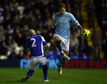 BIRMINGHAM, ENGLAND - FEBRUARY 02:  Edin Dzeko  of Manchester City goes past Stephen Carr of Birmingham during the Barclays premier league match between Birmingham City and Manchester City at St Andrews on February 2, 2011 in Birmingham, England.  (Photo