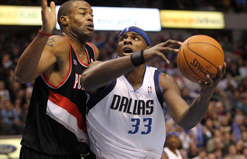 DALLAS, TX - JANUARY 04:  Center Brendan Haywood #33 of the Dallas Mavericks dribbles the ball against Marcus Camby #23 of the Portland Trail Blazers at American Airlines Center on January 4, 2011 in Dallas, Texas.  NOTE TO USER: User expressly acknowledg