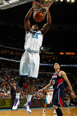 NEW ORLEANS, LA - DECEMBER 26:  D.J. Mbenga #28 of the New Orleans Hornets dunks the ball over Mike Bibby #10 of the Atlanta Hawks at the New Orleans Arena on December 26, 2010 in New Orleans, Louisiana.  NOTE TO USER: User expressly acknowledges and agre