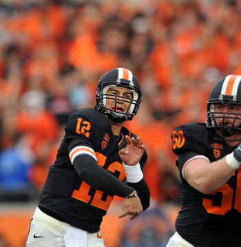 CORVALLIS, OR - DECEMBER 4: Quarterback Ryan Katz #12 of the Oregon State Beavers tries to pass the ball over the outstretched arm of Taylor Hart #66 of the Oregon Ducks in the second quarter the game at Reser Stadium on December 4, 2010 in Corvallis, Ore