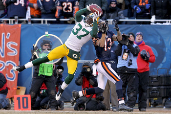 CHICAGO, IL - JANUARY 23:  Sam Shields #37 of the Green Bay Packers intercepts a pass intended for Johnny Knox #13 of the Chicago Bears late in the second quarter in the NFC Championship Game at Soldier Field on January 23, 2011 in Chicago, Illinois.  (Ph